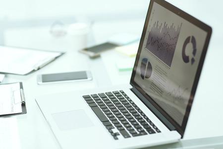 laptop, appunti e dati finanziari sulla scrivania dell'uomo d'affari. Archivio Fotografico
