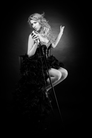 beautiful female singer in black concert dress performing jazz