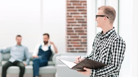 lächelnder Mitarbeiter mit einer Zwischenablage im Büro stehen