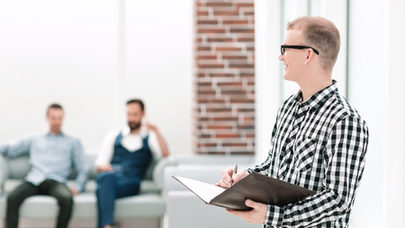 smiling employee with a clipboard standing in the office