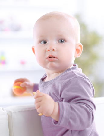 close up.cute baby eating a cookie while sitting on the couch