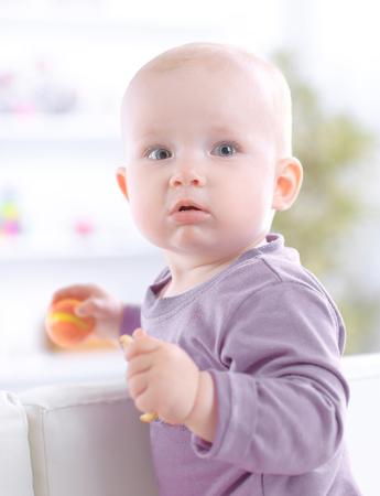 Close up.lindo bebé comiendo una galleta mientras está sentado en el sofá