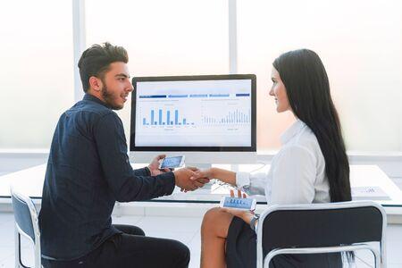 handshake of a businessman and businesswoman near office Desk.