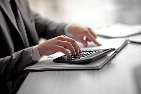 avvicinamento. l'uomo d'affari può usare la calcolatrice per calcolare il profitto