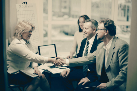 Business handshake women with a partner over a Desk Imagens - 124688916