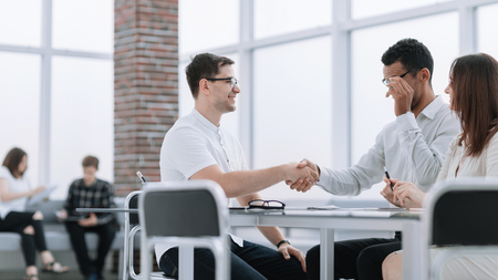 Smiling business partners shaking hands during the meeting