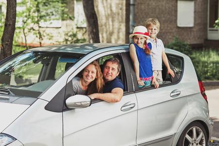 Familia con dos hijos sentados en su coche familiar.