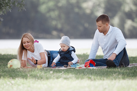Loving parents and their little son sitting on the lawn on a summer day. Stock Photo