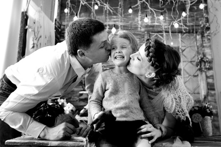 Mom and dad kissing his little daughter.