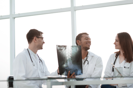 Smiling group of doctors discussing the patients x-ray