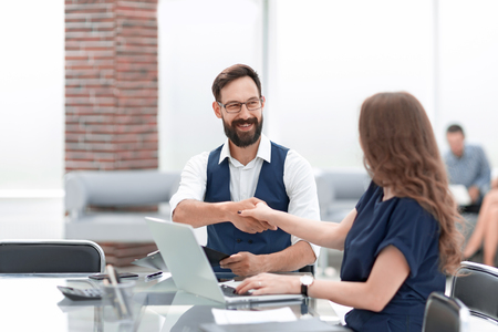 Businessman and businesswoman shaking hands over the Desk Imagens