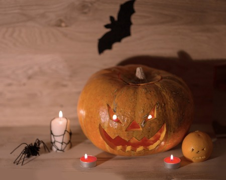 Candles, pumpkins and a spider on a wooden Reklamní fotografie