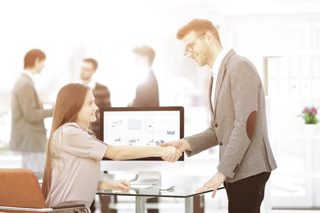 Manager and employee shaking hands to each other as a sign of success