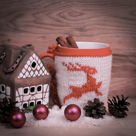 Christmas Cup and a gingerbread house on a wooden table .
