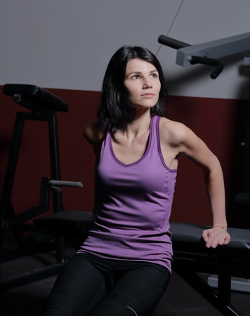 Young sporty woman sitting on the floor in the fitness center.
