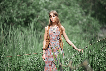 Beautiful hippie girl standing on a wooden bridge in the Park