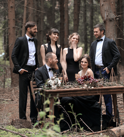 Guests and a couple of newlyweds near the picnic table in the woods
