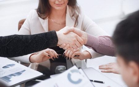 Handshake of the Manager and the client at the table in the Bank office Imagens