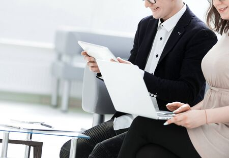 business colleagues use gadgets sitting in the office hall