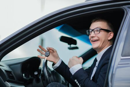 happy businessman holding keys to his new car