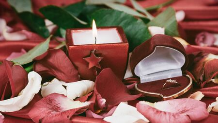 candle and a diamond ring on a background of rose petals