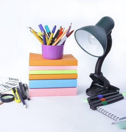 Table lamp and school supplies on white Stock Photo