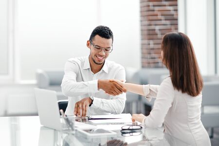 handshake business colleagues for a work Desk
