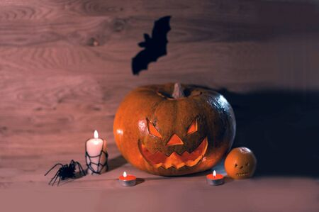 candles,pumpkins and a spider on a wooden background