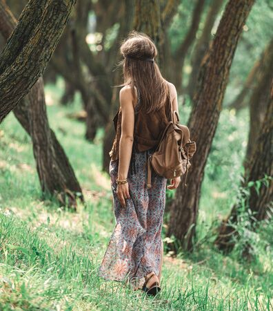 attractive hippie girl walking among the trees in the forest