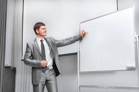 selbstbewusster Geschäftsmann, der auf der Bühne im Konferenzsaal steht