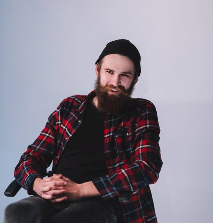 hipster in jeans and plaid shirt sitting in a chair