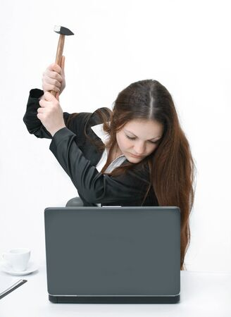 young business woman trying to smash the laptop with a hammer