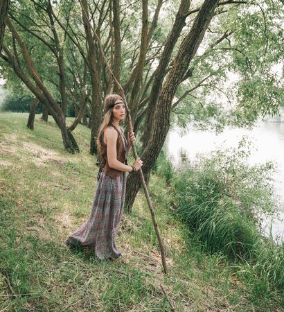 young hippie woman standing near forest lake