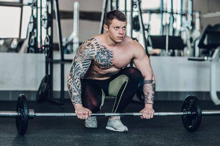 männlicher Bodybuilder, der sich darauf vorbereitet, die Messlatte anzuheben.