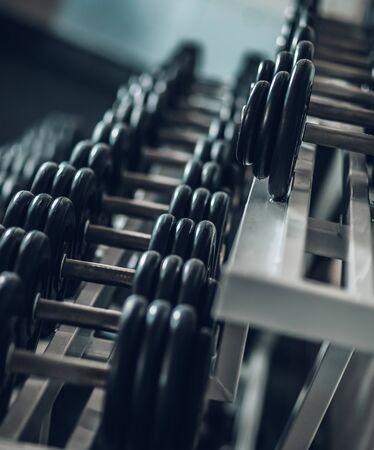 fermer. Des rangées d'haltères dans la salle de gym.