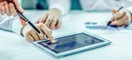 businessman using digital tablet, working with the financial sch