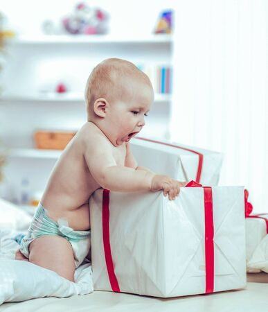 one year old cute baby playing with shopping in boxes on the sof