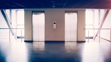 Glass wall with two elevators in the office building, there is a