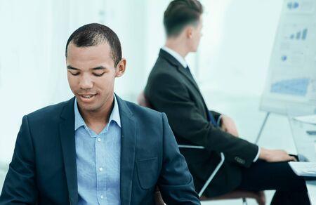 vielversprechender junger Mitarbeiter, der hinter einem Schreibtisch sitzt Standard-Bild