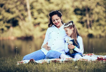 concept of maternity - pregnant mother and little daughter having fun outdoors