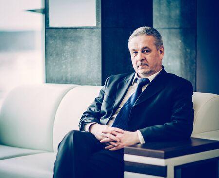 successful businessman sitting in chair modern office
