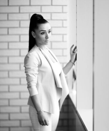 modern business woman standing near the window in the corridor