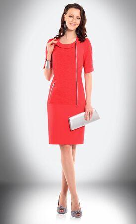 elegant woman model in red dress and with stylish handbag 免版税图像