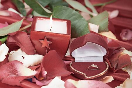 candle and a diamond ring on a background of rose petals Stockfoto