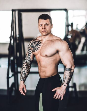 Beautiful bodybuilder trainer showing off his body