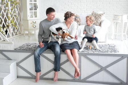 Parents and little girl playing with a dog