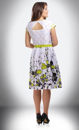 in full growth. charming woman in summer dress with floral pattern