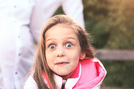 portrait of a surprised little girl on a walk in the Park on a S