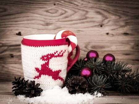 Christmas mug with Christmas decorations in wooden background