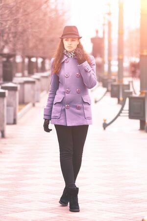 Beautiful girl in a hat, walking down the street.